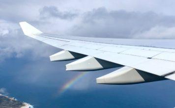aile d'avion avec arc en ciel et mer en fond