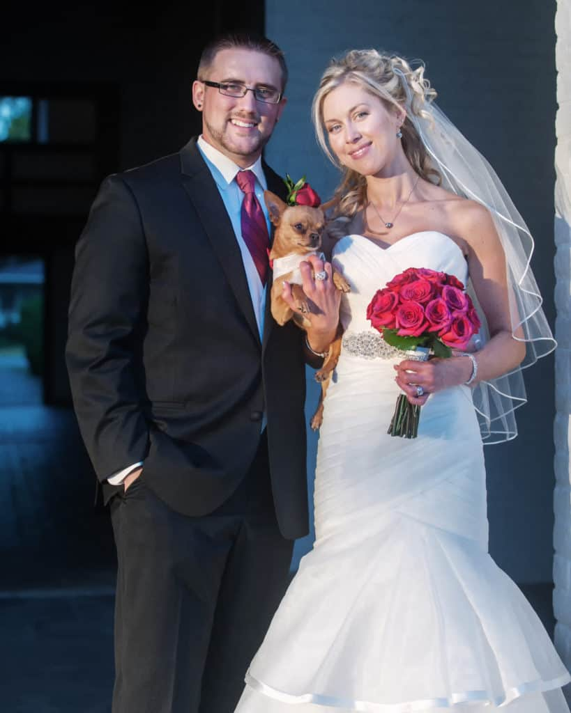 bride and groom glowing, holding their beloved chihuahua. sweet wedding photo.
